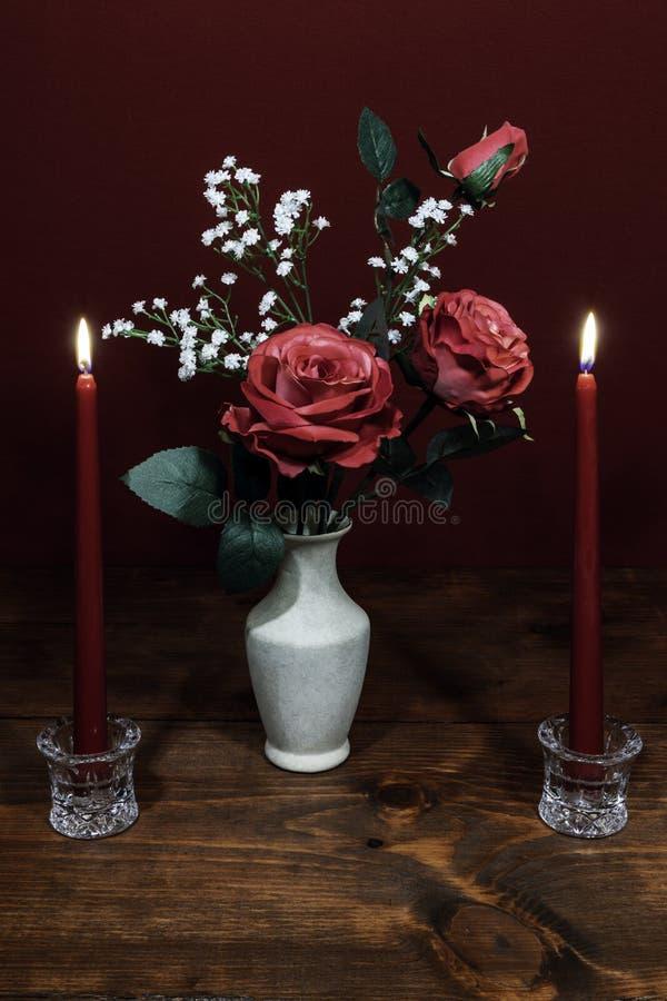 Τα όμορφα ρόδινα τριαντάφυλλα σε ένα βάζο με τα λουλούδια αναπνοής του μωρού, δύο κόκκινα κεριά στον κάτοχο κρυστάλλου στοκ φωτογραφία
