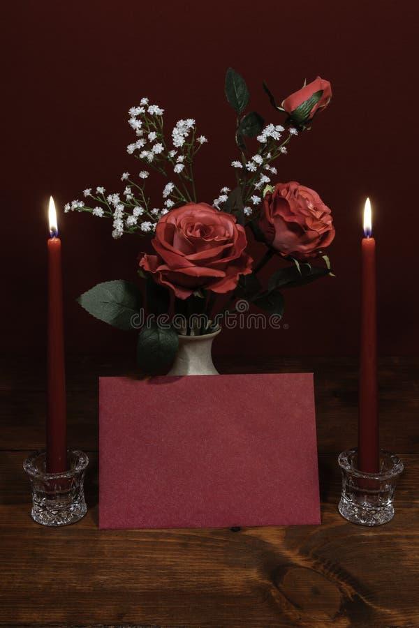 Τα όμορφα ρόδινα τριαντάφυλλα σε ένα βάζο που τονίζεται με την αναπνοή του μωρού ανθίζουν, δύο αναμμένα ed κεριά στον κάτοχο κρυσ στοκ φωτογραφίες