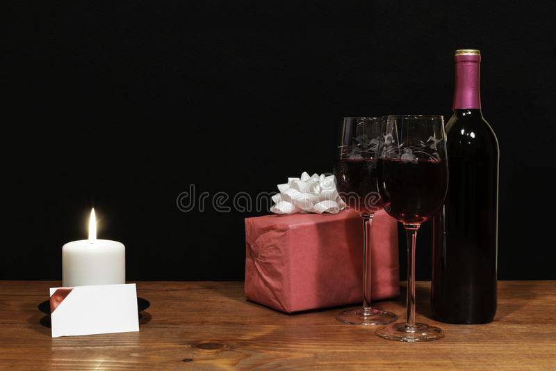 Τα όμορφα χαραγμένα γυαλιά κρασιού και το μπουκάλι του κόκκινου κρασιού, άσπρο κερί, τύλιξαν το παρόν με το τόξο στον ξύλινο πίνα στοκ φωτογραφία με δικαίωμα ελεύθερης χρήσης