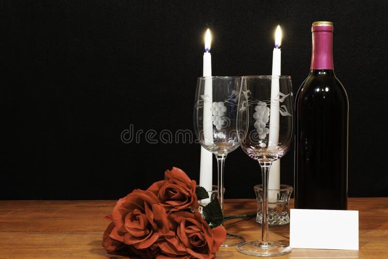Τα όμορφα χαραγμένα γυαλιά κρασιού και το μπουκάλι του κόκκινου κρασιού, των άσπρων κεριών και των κόκκινων τριαντάφυλλων στον ξύ στοκ φωτογραφίες με δικαίωμα ελεύθερης χρήσης