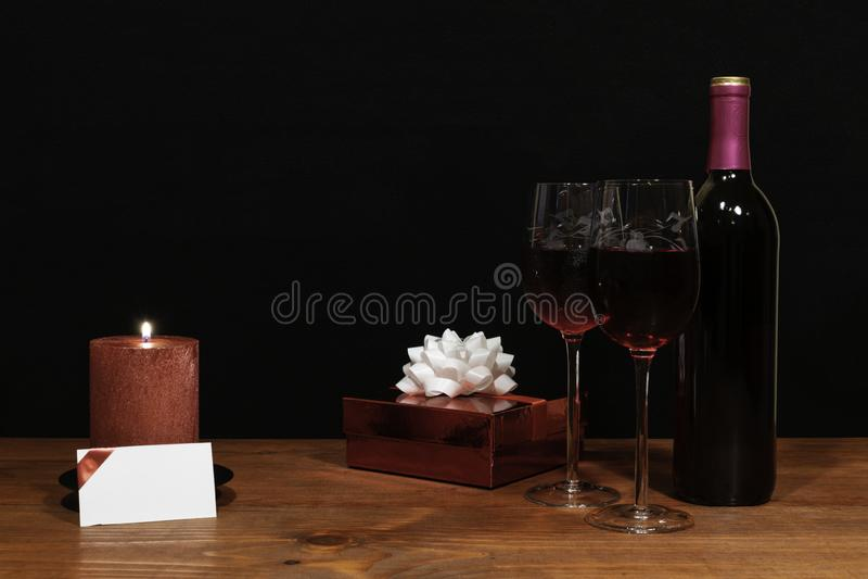Τα όμορφα χαραγμένα γυαλιά κρασιού και το μπουκάλι του κόκκινου κρασιού, κόκκινο κερί, τύλιξαν το παρόν με το τόξο στον ξύλινο πί στοκ εικόνες