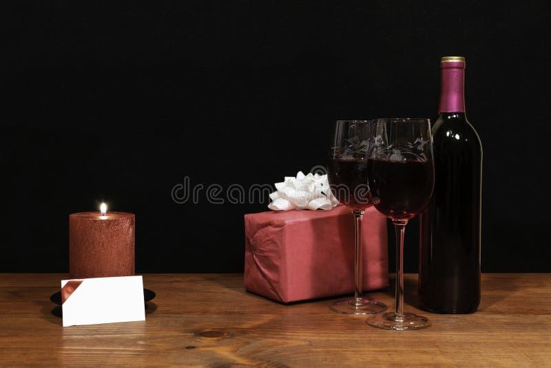 Τα όμορφα χαραγμένα γυαλιά κρασιού και το μπουκάλι του κόκκινου κρασιού, κόκκινο κερί, τύλιξαν το παρόν με το τόξο στον ξύλινο πί στοκ φωτογραφία με δικαίωμα ελεύθερης χρήσης