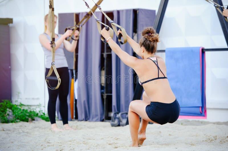 Τα όπλα γυναικών workout με τις ζώνες ικανότητας trx στη φύση αποτελούν μια ώθηση τους ανώτερους δικέφαλους μυς θωρακικών ώμων ρυ στοκ φωτογραφία με δικαίωμα ελεύθερης χρήσης
