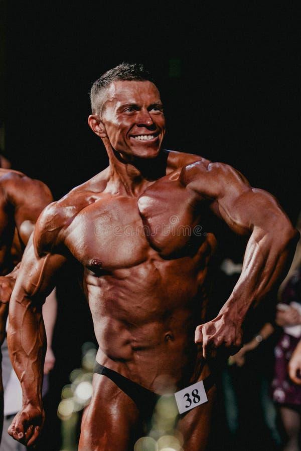 Τα bodybuilders αθλητών χαμόγελου τεντώνουν το στήθος και τον Τύπο σας στοκ φωτογραφίες