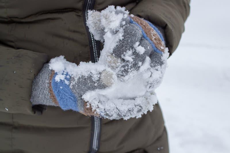 Τα sculpts μια χιονιά, μια γυναίκα που φορά τα γάντια παίρνουν το χιόνι στοκ φωτογραφίες με δικαίωμα ελεύθερης χρήσης