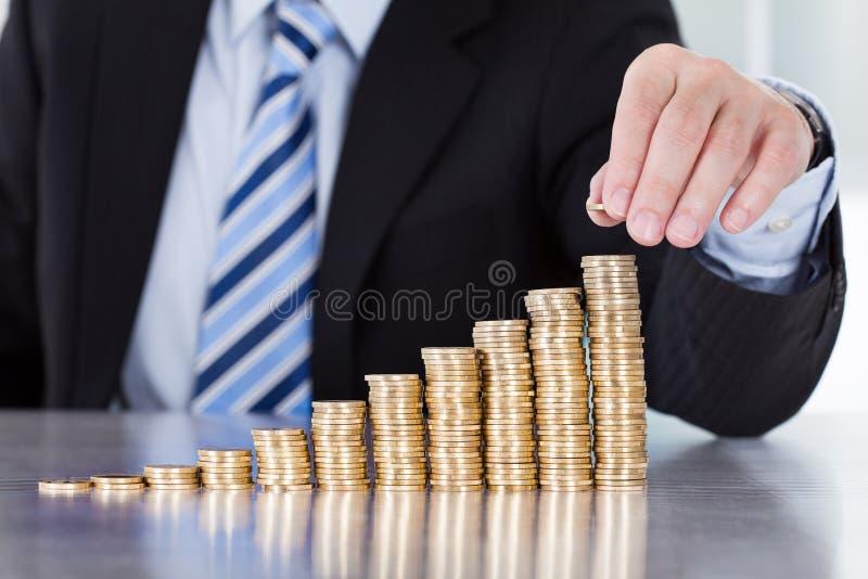 Τεθειμένα χέρι νομίσματα επιχειρηματιών στο σωρό των νομισμάτων στοκ εικόνες
