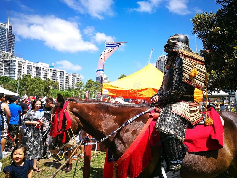 Τεθωρακισμένο Σαμουράι cosplay στο άλογο Η εικόνα στο ιαπωνικό φεστιβάλ Matsuri στοκ εικόνες
