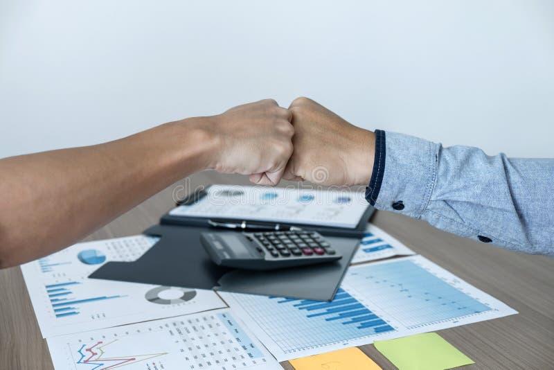 Τελειώνοντας επάνω μια συνεδρίαση, που δίνει την πρώτη πρόσκρουση δύο ευτυχών επιχειρηματιών του χεριού μετά από το συμφωνητικό σ στοκ εικόνα