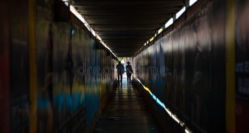 τελειώστε την ελαφριά σήραγγα Νέο ζεύγος που περπατά σε μια σκοτεινή προστατευτική μετάβαση στοκ εικόνες