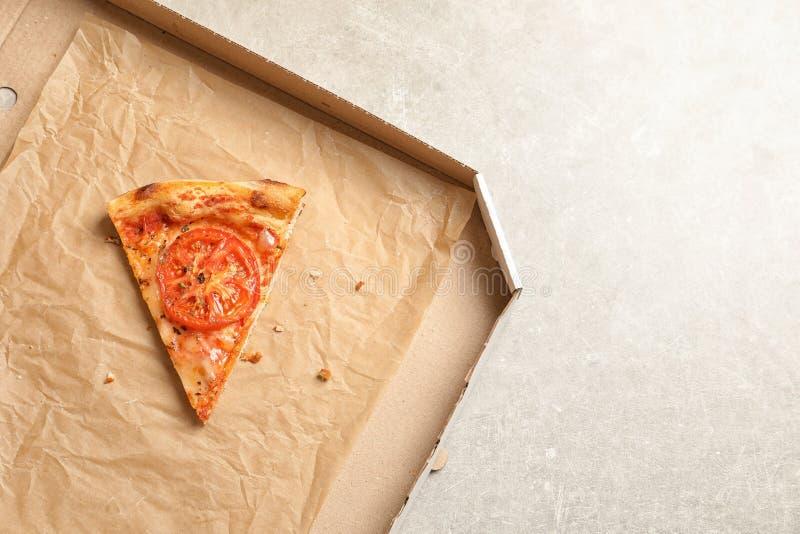 Τελευταία φέτα της πίτσας τυριών στο κουτί από χαρτόνι στην γκρίζα, τοπ άποψη με το διάστημα για το κείμενο Υπηρεσία παράδοσης τρ στοκ φωτογραφία με δικαίωμα ελεύθερης χρήσης