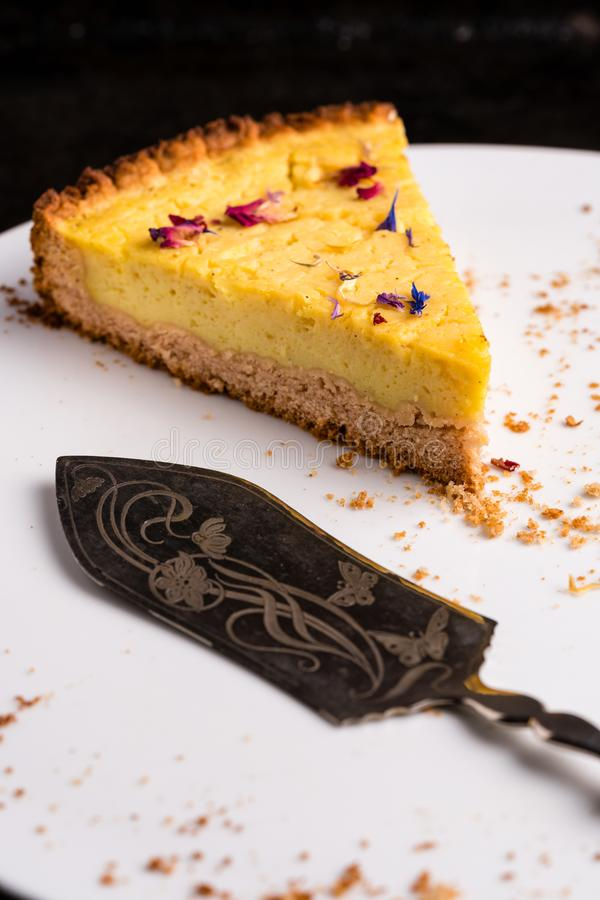 Τελευταίο κομμάτι vegan cheesecake λεμονιών - κατακόρυφος στοκ εικόνες