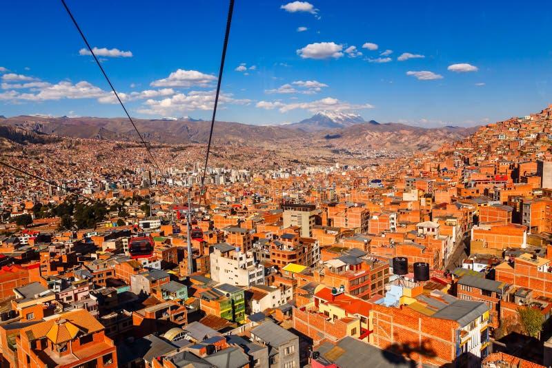 Τελεφερίκ ή τελεφερίκ σύστημα πέρα από τις πορτοκαλιά στέγες και τα κτήρια του βολιβιανού κεφαλαίου, Λα Παζ, Βολιβία στοκ εικόνα με δικαίωμα ελεύθερης χρήσης