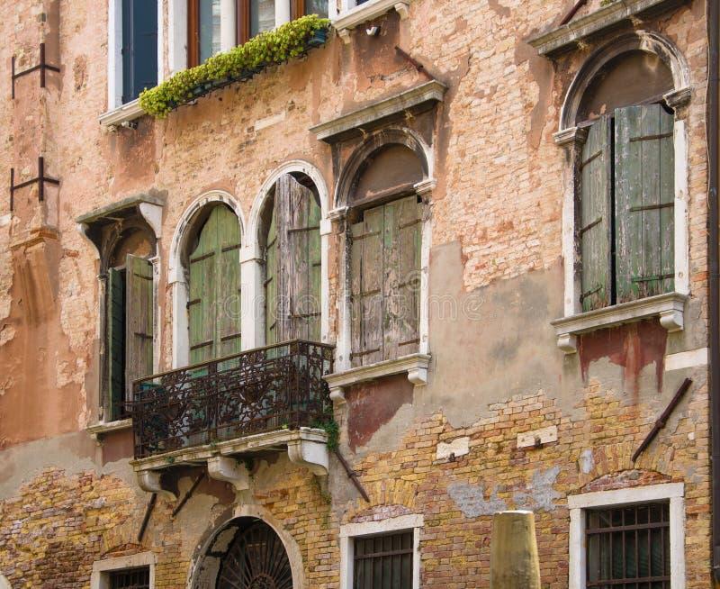 Τεμάχιο ενός παλαιού σπιτιού με τα ξύλινα παραθυρόφυλλα στα παράθυρα και τις πόρτες στοκ φωτογραφία