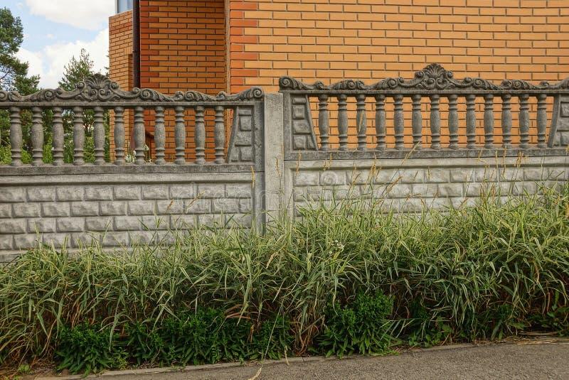 Τεμάχιο του γκρίζου συγκεκριμένου φράκτη έξω στη χλόη στοκ φωτογραφία με δικαίωμα ελεύθερης χρήσης