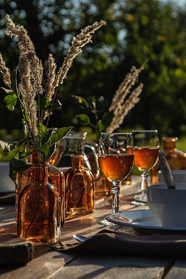 Τεμάχιο του πίνακα που θέτει με τα πιάτα, γυαλιά κρασιού, μπουκάλια στον κήπο για το γεύμα στο ηλιοβασίλεμα στοκ φωτογραφίες