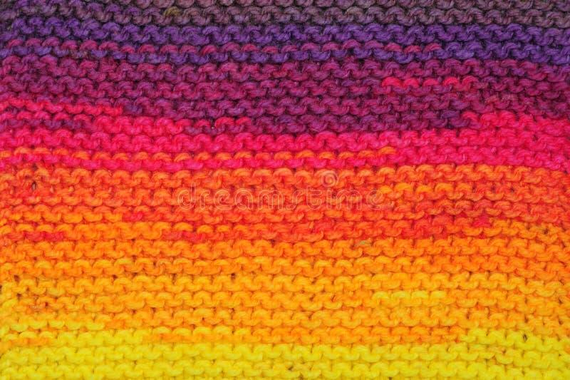 Τεμάχιο των χειροποίητων άνευ ραφής πλεκτών σχεδίων στο μίγμα χρωμάτων ηλιοβασιλέματος ουράνιων τόξων στοκ εικόνες