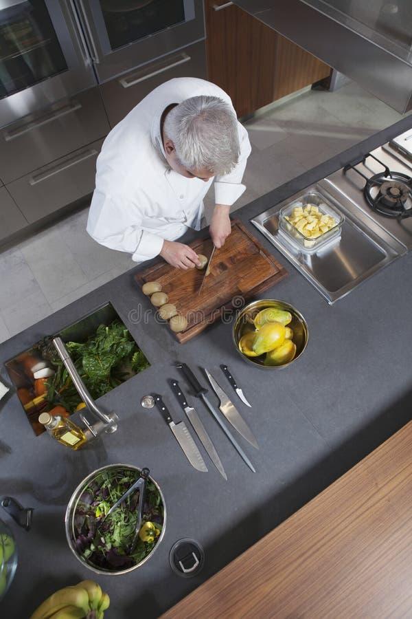Τεμαχίζοντας ακτινίδιο αρχιμαγείρων εν πλω στον εμπορικό μετρητή κουζινών στοκ φωτογραφία