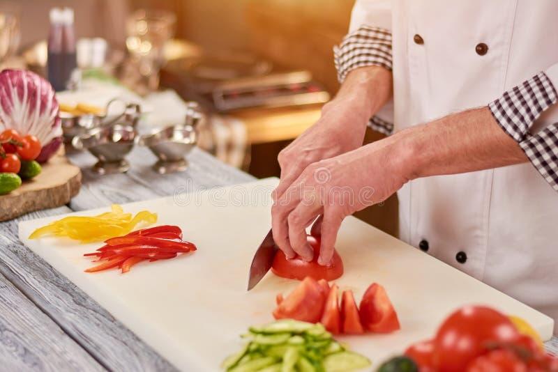 Τεμαχίζοντας ντομάτα αρχιμαγείρων στον τέμνοντα πίνακα στοκ φωτογραφία με δικαίωμα ελεύθερης χρήσης