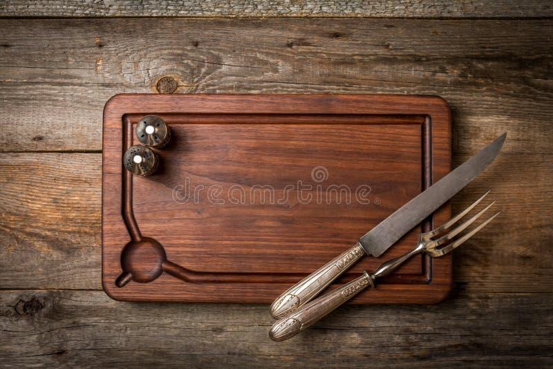 Τεμαχίζοντας τέμνοντες πίνακας, καρυκεύματα και δίκρανο και μαχαίρι κρέατος στοκ εικόνα