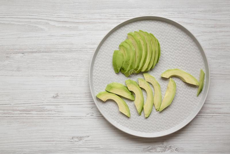 Τεμαχισμένα αβοκάντο σε ένα πιάτο πέρα από το άσπρο ξύλινο υπόβαθρο, τοπ άποψη Υπερυψωμένος, άνωθεν, επίπεδος βάζει r στοκ φωτογραφίες με δικαίωμα ελεύθερης χρήσης