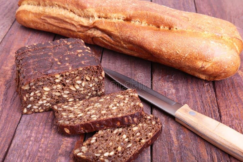 Τεμαχισμένα μαύρα ψωμί και μαχαίρι στην παλαιά ξύλινη σανίδα στοκ φωτογραφία