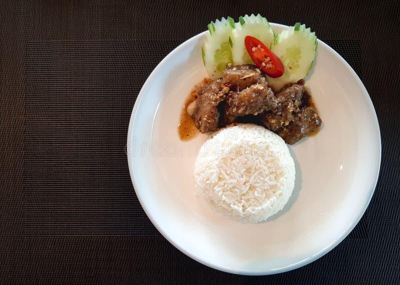 Τεμαχισμένα πλευρά χοιρινού κρέατος που τηγανίζονται με το ζωμό σκόρδου που εξυπηρετείται με το ρύζι στοκ εικόνα