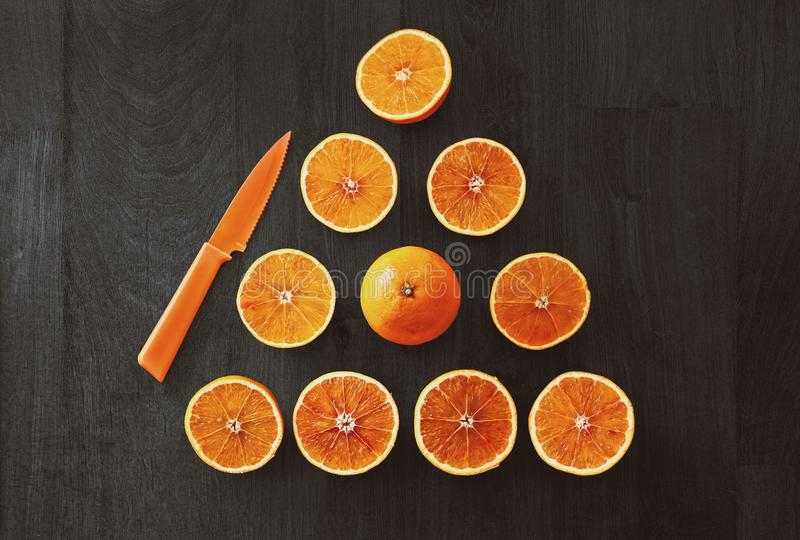 Τεμαχισμένα πορτοκαλιά φρούτα με το μαχαίρι στοκ φωτογραφίες