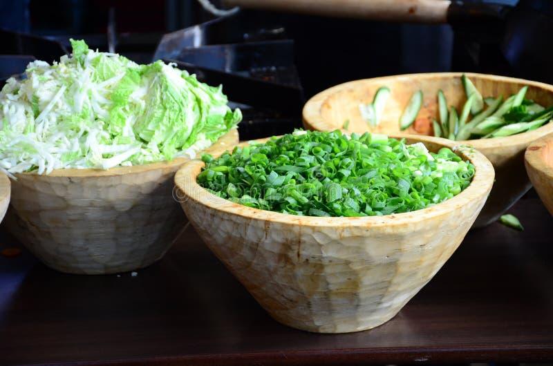 Τεμαχισμένα, τεμαχισμένα κρεμμύδια άνοιξη, κρεμμύδια σαλάτας, πράσινα κρεμμύδια ή scallions σε ένα ξύλινο κύπελλο στοκ φωτογραφία