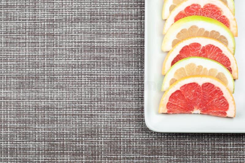 Τεμαχισμένες φρέσκες φέτες γκρέιπφρουτ σε ένα άσπρο πιάτο στοκ εικόνες