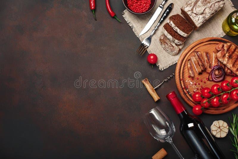 Τεμαχισμένες ψημένες στη σχάρα μπριζόλες χοιρινού κρέατος με το μπουκάλι του κρασιού, γυαλί κρασιού, ανοιχτήρι, μαχαίρι, δίκρανο, στοκ φωτογραφίες