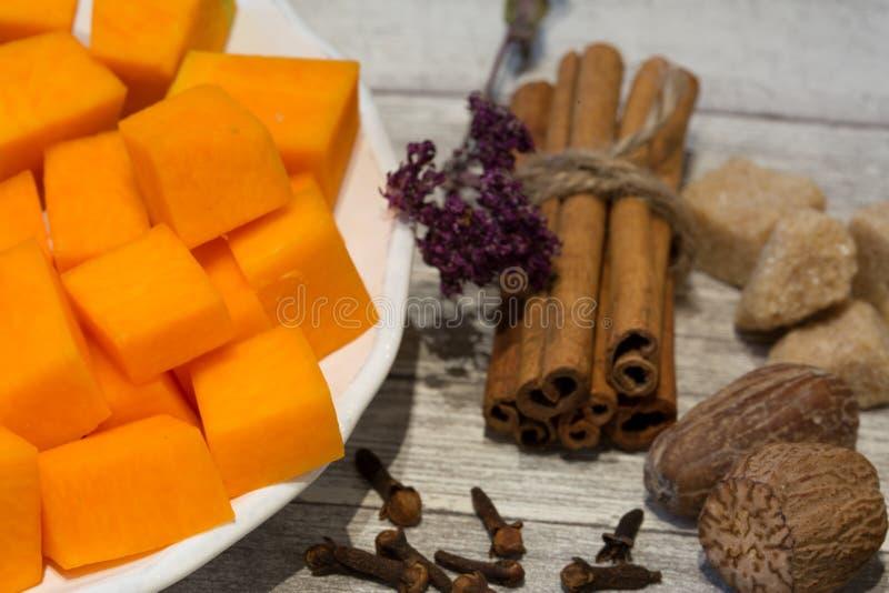Τεμαχισμένη κολοκύθα στο άσπρο πιάτο με τα ραβδιά κανέλας, αστέρι γλυκάνισου, στοκ φωτογραφία