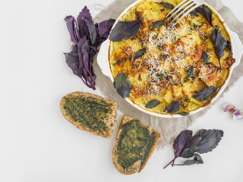 Τεμαχισμένη πατάτα που ψήνεται με το τυρί και το βασιλικό στο φούρνο στοκ φωτογραφία