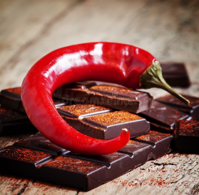 Τεμαχισμένη σκοτεινή σοκολάτα, κόκκινο πιπέρι τσίλι και κόκκινο πιπέρι, selecti στοκ φωτογραφία