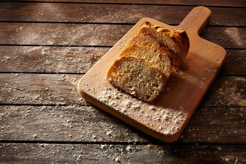Τεμαχισμένη ψωμί φραντζόλα στον ξύλινο πίνακα στο αγροτικό ξύλο στοκ εικόνες