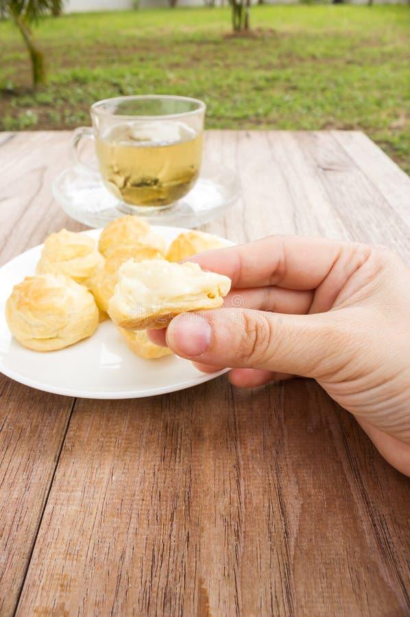 Τεμαχισμένη choux κρέμα γυναίκας μάζεμα με το χέρι στοκ φωτογραφία