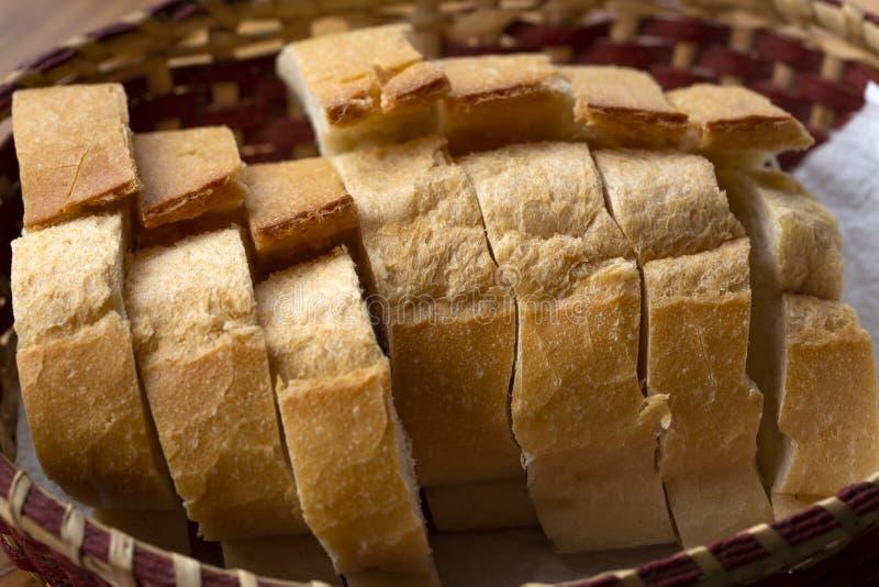 Τεμαχισμένος γύρω από τη φραντζόλα του ψωμιού σίκαλης με μια ορεκτική τριζάτη καφετιά κρούστα σε ένα γκρίζο τραπεζομάντιλο λινού στοκ εικόνες
