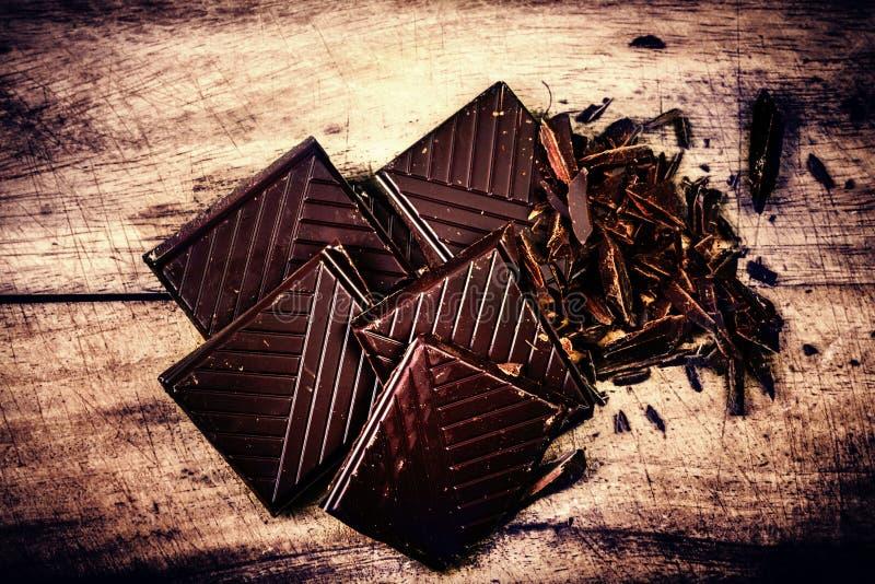 Τεμαχισμένος φραγμός σοκολάτας στην ξύλινη κινηματογράφηση σε πρώτο πλάνο υποβάθρου. Σπασμένο σκοτάδι στοκ εικόνες με δικαίωμα ελεύθερης χρήσης