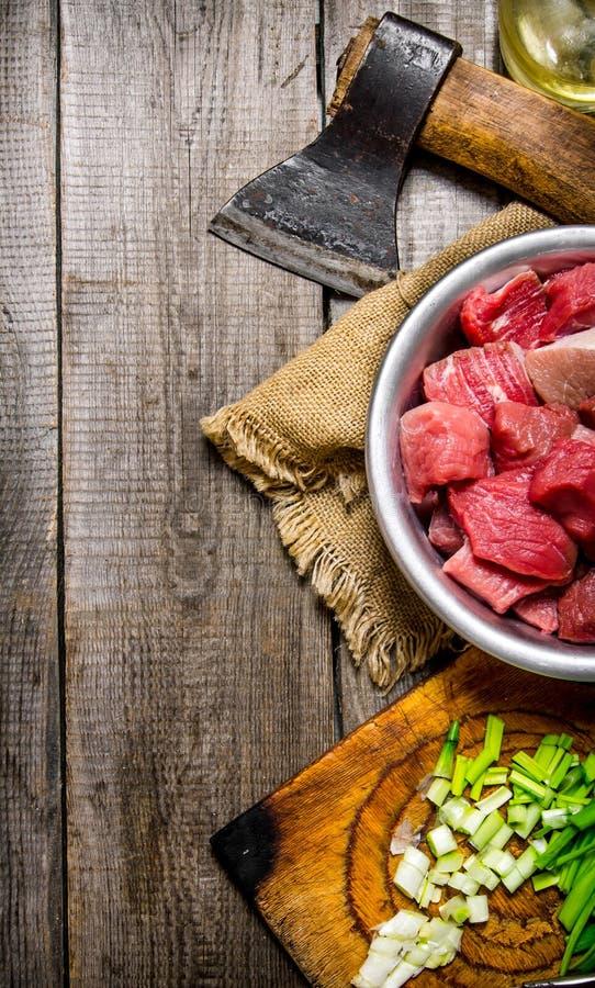 Τεμαχισμένο ακατέργαστο κρέας με τα φρέσκα κρεμμύδια και ένα τσεκούρι σε ένα παλαιό ύφασμα στοκ φωτογραφία με δικαίωμα ελεύθερης χρήσης