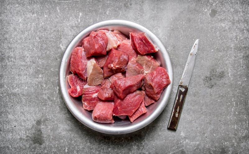Τεμαχισμένο ακατέργαστο κρέας σε ένα κύπελλο με ένα μαχαίρι στοκ εικόνες
