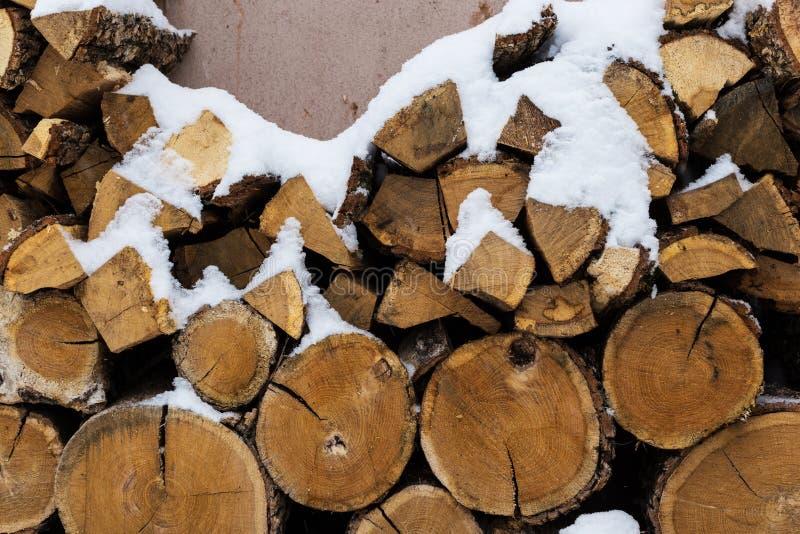 Τεμαχισμένο απόθεμα του καυσόξυλου κάτω από το χιόνι στην οδό Καυσόξυλο για την εστία και bbq στοκ εικόνα