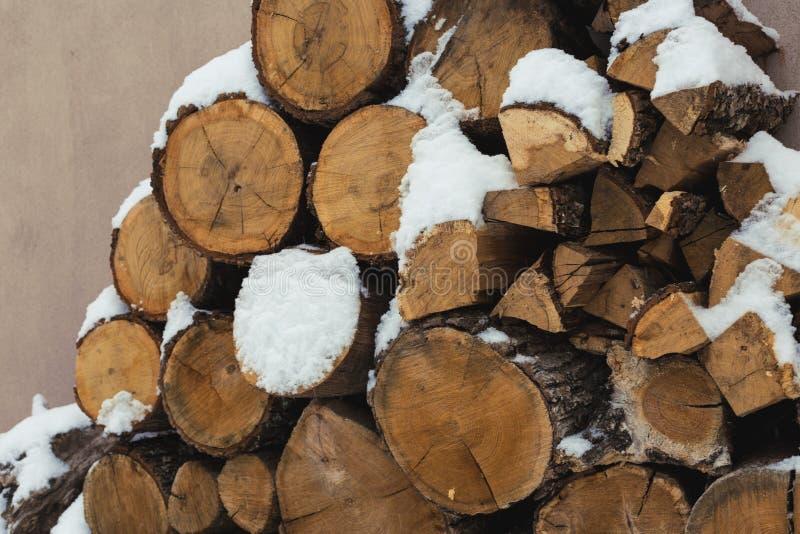 Τεμαχισμένο απόθεμα του καυσόξυλου κάτω από το χιόνι στην οδό Καυσόξυλο για την εστία και bbq στοκ φωτογραφία με δικαίωμα ελεύθερης χρήσης