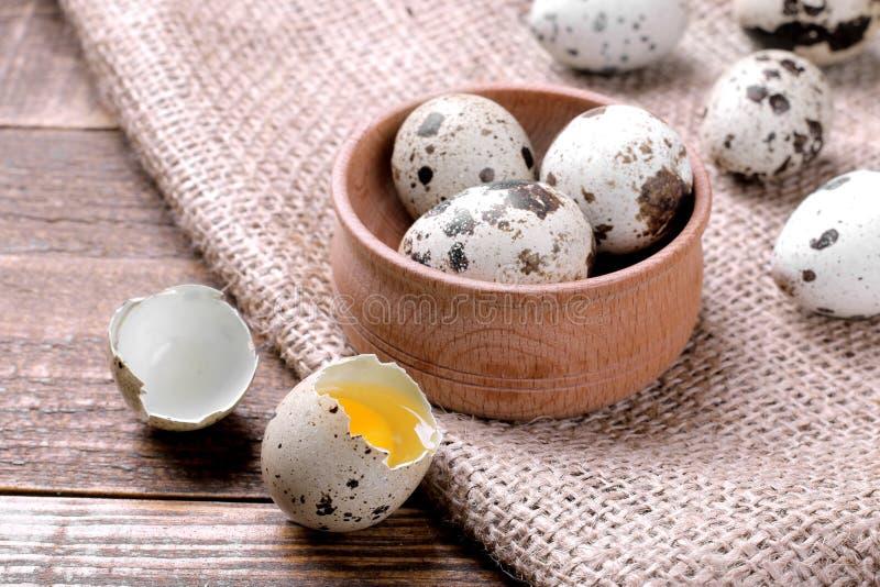 Τεμαχισμένο αυγό ορτυκιών με την κινηματογράφηση σε πρώτο πλάνο λέκιθου δίπλα σε ένα ξύλινο κύπελλο με τα αυγά σε ένα καφετί υπόβ στοκ φωτογραφία