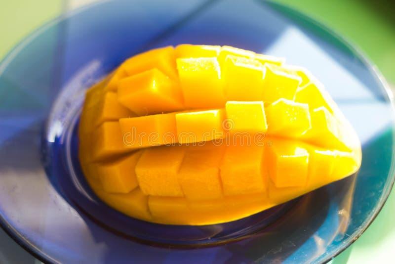 Τεμαχισμένο μάγκο στον ήλιο σε ένα μπλε πιάτο στοκ εικόνες