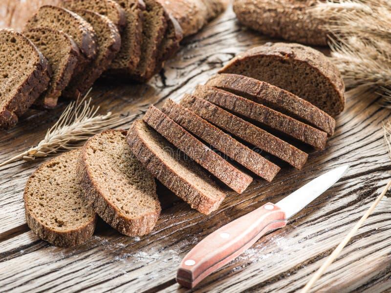 Τεμαχισμένο μαύρο ψωμί στην ξύλινη σανίδα στοκ εικόνες