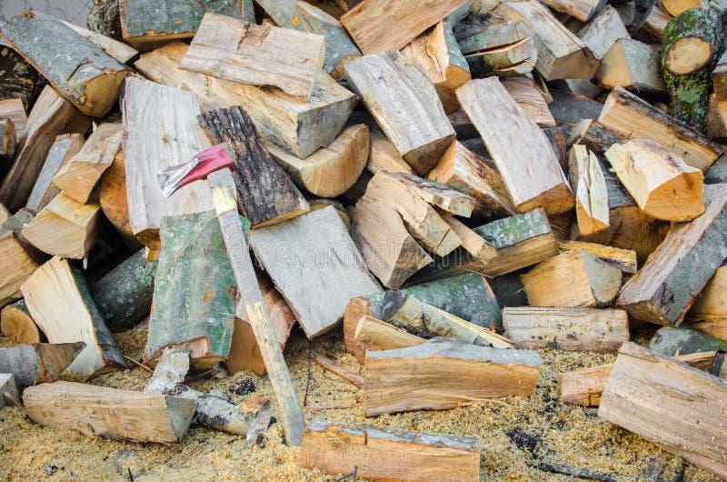 Τεμαχισμένο ξύλο πυρκαγιάς σε έναν σωρό με ένα τσεκούρι στοκ εικόνες