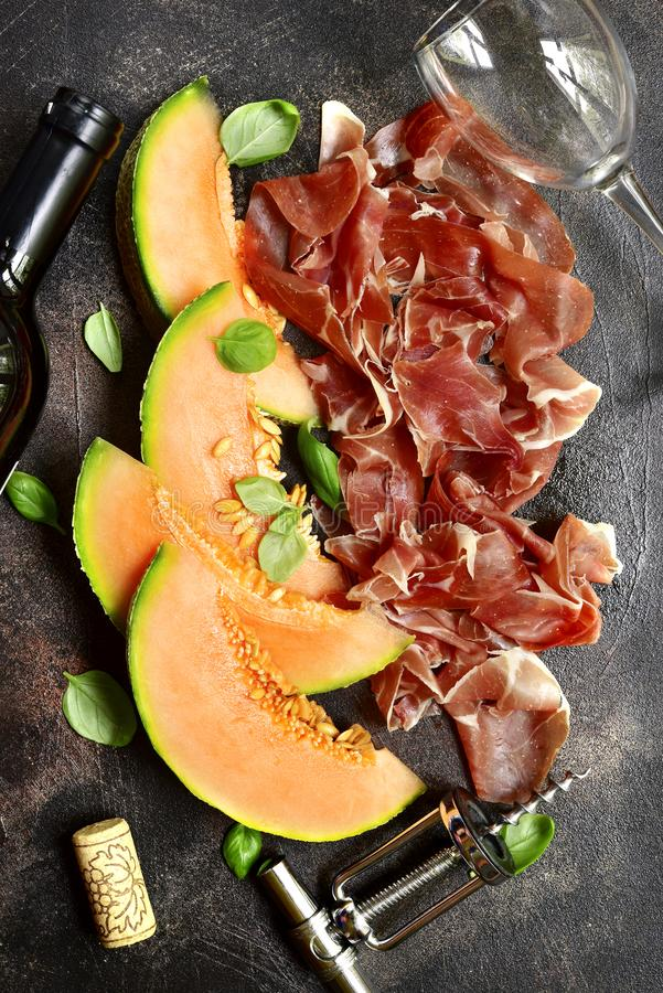 Τεμαχισμένο πεπόνι και jamon ή prosciutto με το μπουκάλι του κόκκινου κρασιού κορυφή στοκ εικόνες