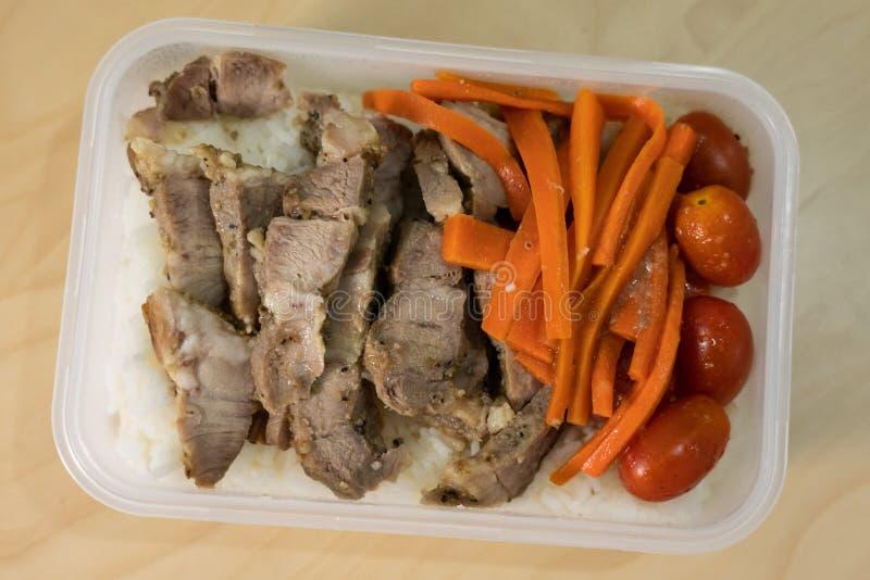 Τεμαχισμένο τηγανισμένο χοιρινό κρέας που εξυπηρετείται με τα καρότα και τις ντομάτες στο ρύζι στοκ εικόνες με δικαίωμα ελεύθερης χρήσης