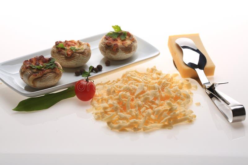 Τεμαχισμένο τυρί δίπλα σε ένα πιάτο με τα κεφάλια μανιταριών στοκ εικόνες με δικαίωμα ελεύθερης χρήσης