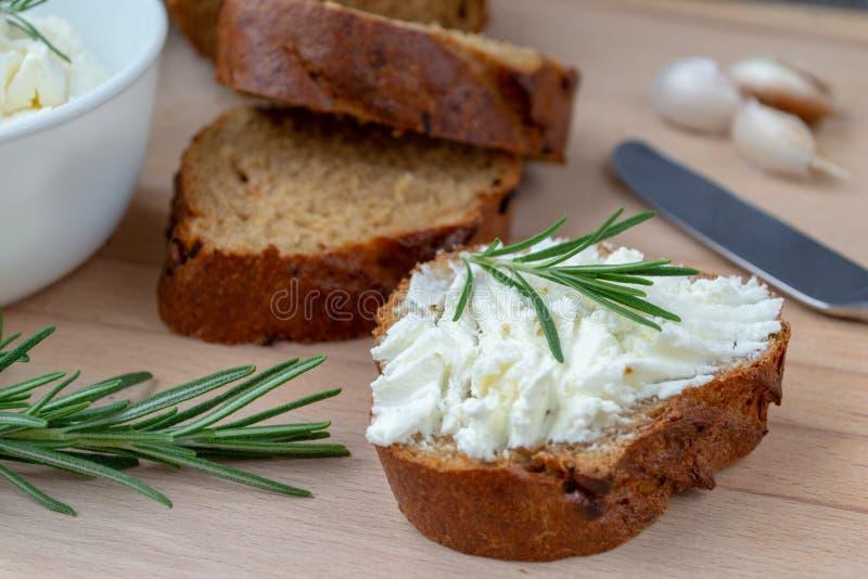 Τεμαχισμένο ψωμί με το ελαφρύ τυρί σε έναν ξύλινο πίνακα στοκ φωτογραφία