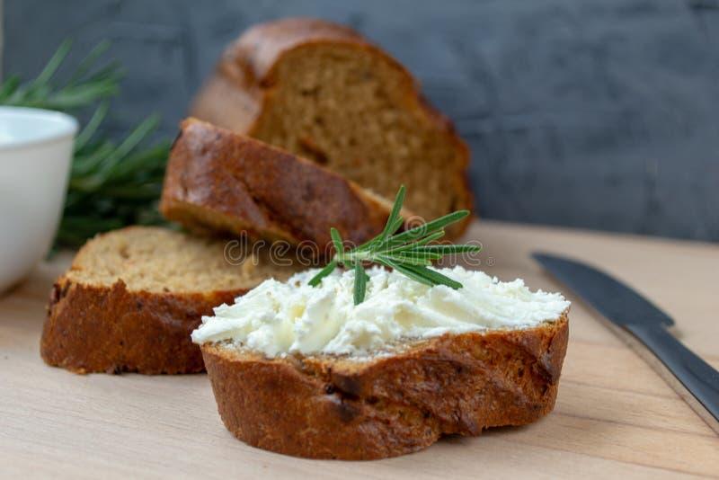 Τεμαχισμένο ψωμί με το ελαφρύ τυρί σε έναν ξύλινο πίνακα στοκ εικόνα
